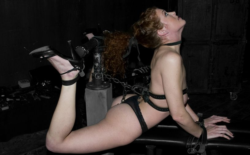Woman is in extreme bondage hogtie : tied with belts and chains