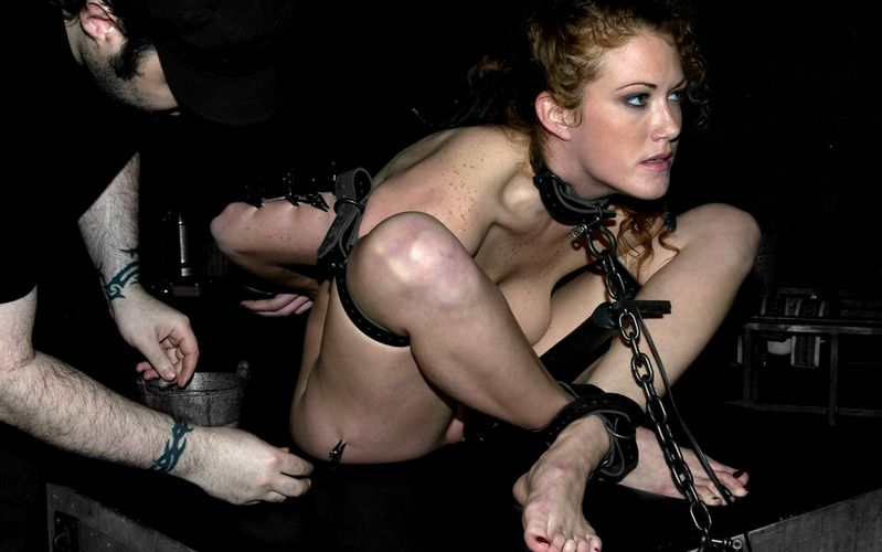 Curly redhead is put in to bondage ball tie with lots of leather belts