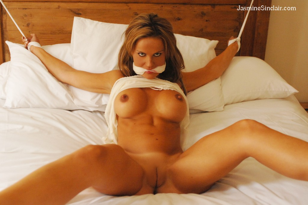 Helpless female tied spread eagle in her bed