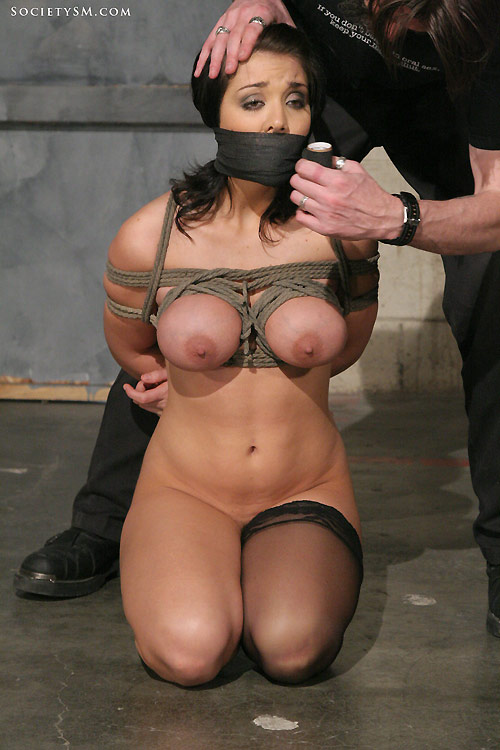 Kneeling breast bondage slave wearing one stocking