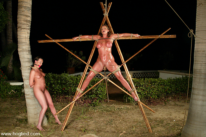 Wooden rack is used for tying up a sexy busty woman