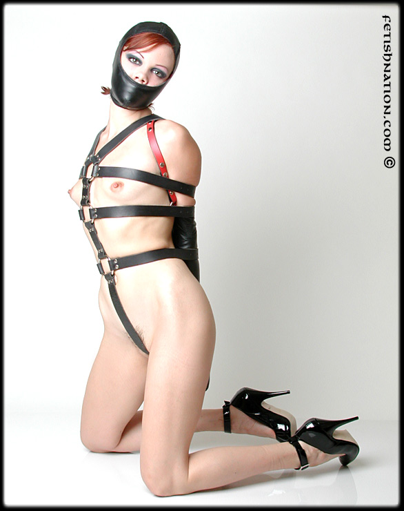Naked girl restrained with armbinder and bady harness