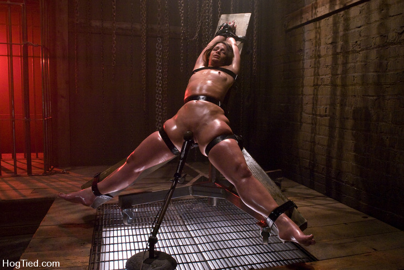 Oiled female bound to one of most bizarre torture devices