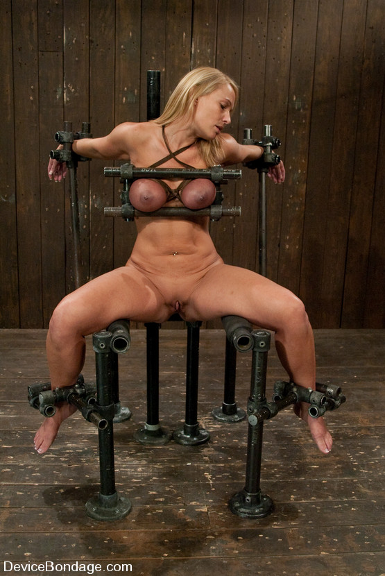 Exposed MILF babe locked in bizarre torture device