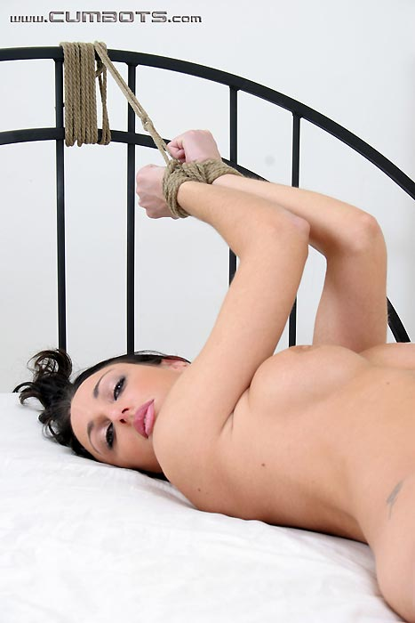 Fully undressed young woman is tied to bed with rope