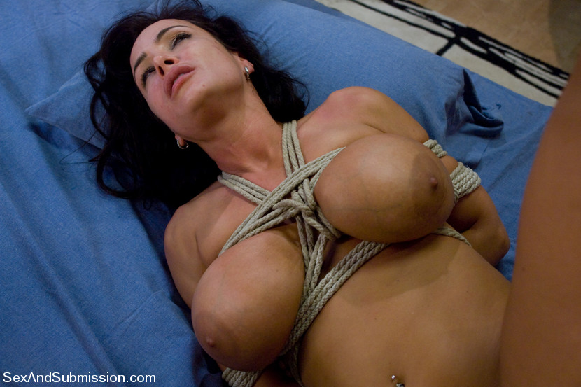 Busty nude woman is tied to bed for degrading bondage fucking