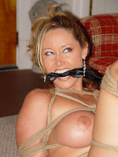 Busty MILF slave gagged with scarf in the middle of bondage training