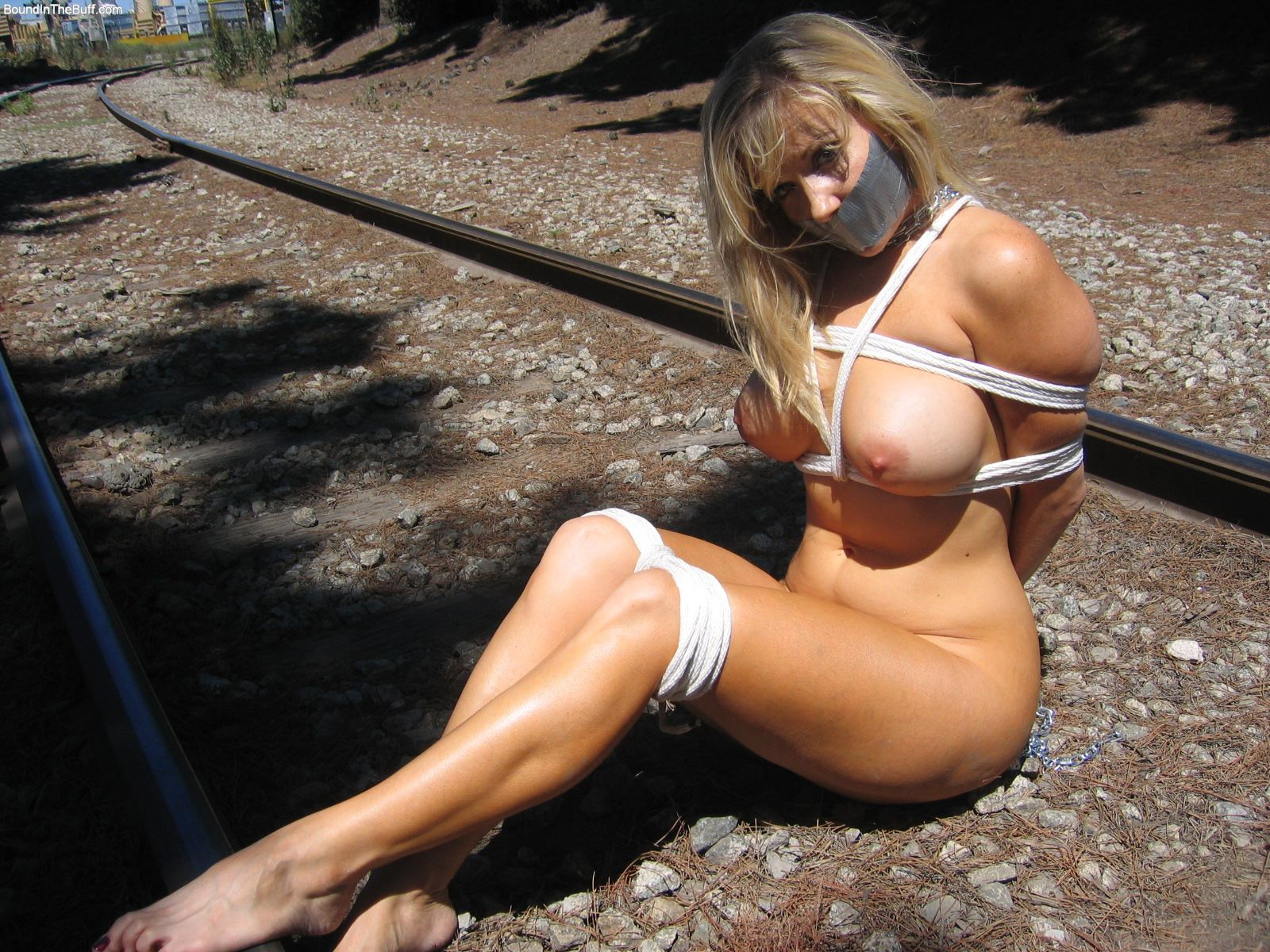 Abducted MILF is put in bondage, gagged and exposed to danger