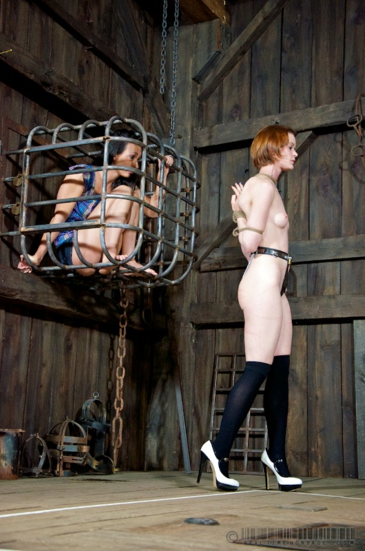 Girl is having her hands drawn back under the unnatural angle and tied with rope