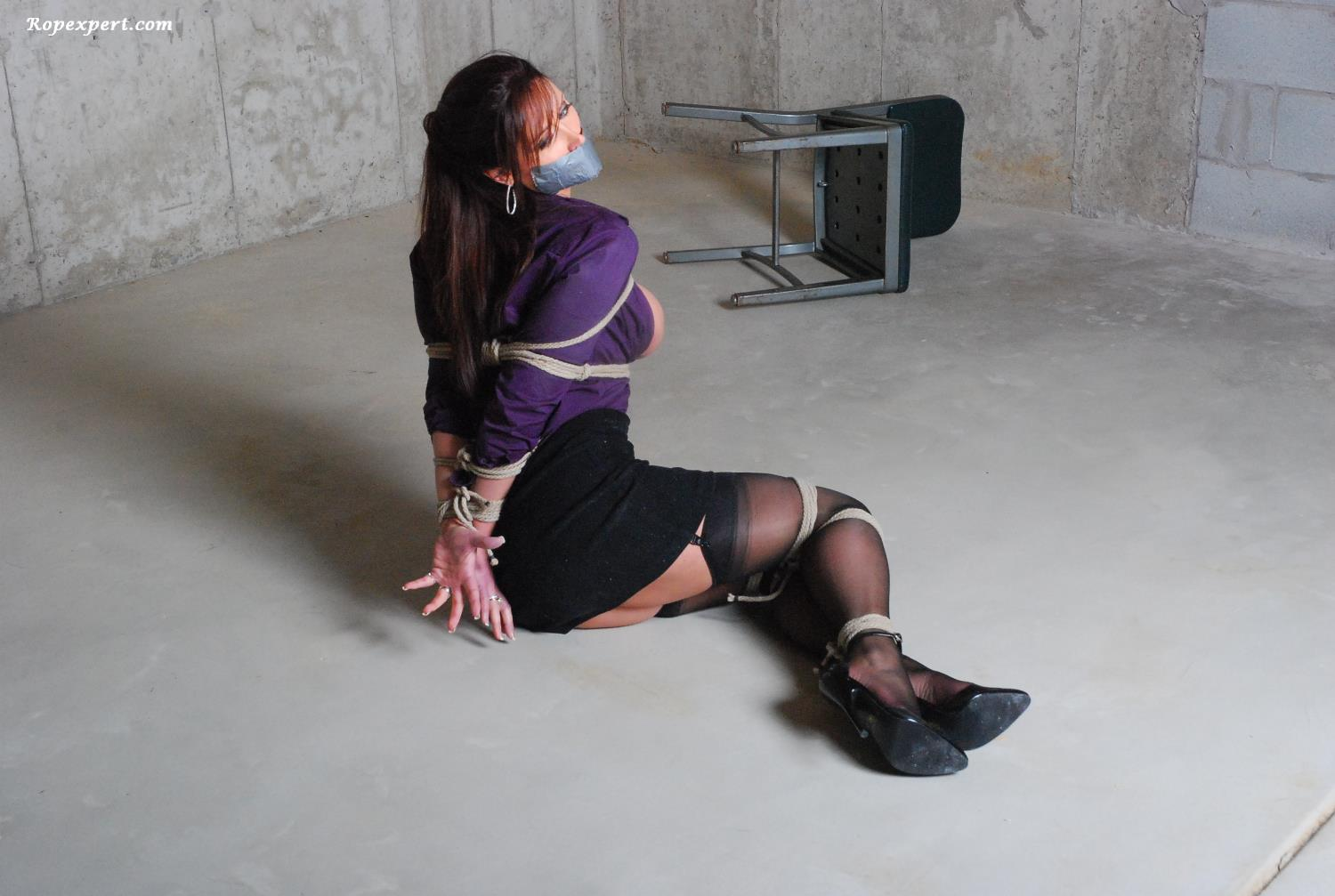Girl in sexy clothes is trying to escape the bondage desperately