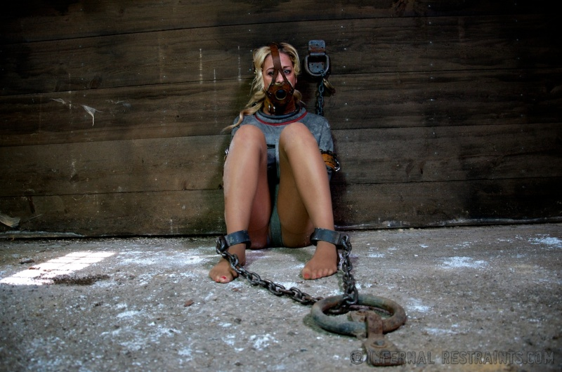 Blonde woman is helplessly restrained with steel shackles and a straightjacket