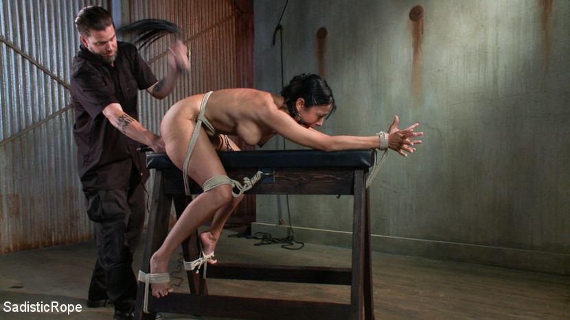 Woman is tied to the wooden horse, her ass in fingered and whipped