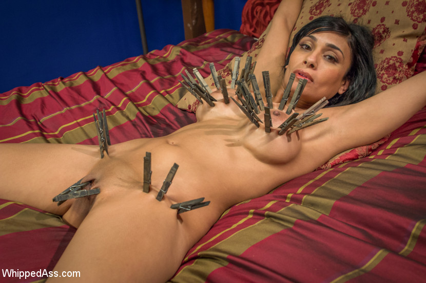 Loads of clothespins are attached to big tits of the bed-bound MILF slave