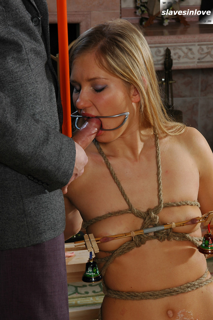 Bondaged girl is doing a blowjob with her mouth spread wide