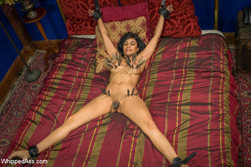 MILF woman is nude and tied to bed posts with her wrists and ankles