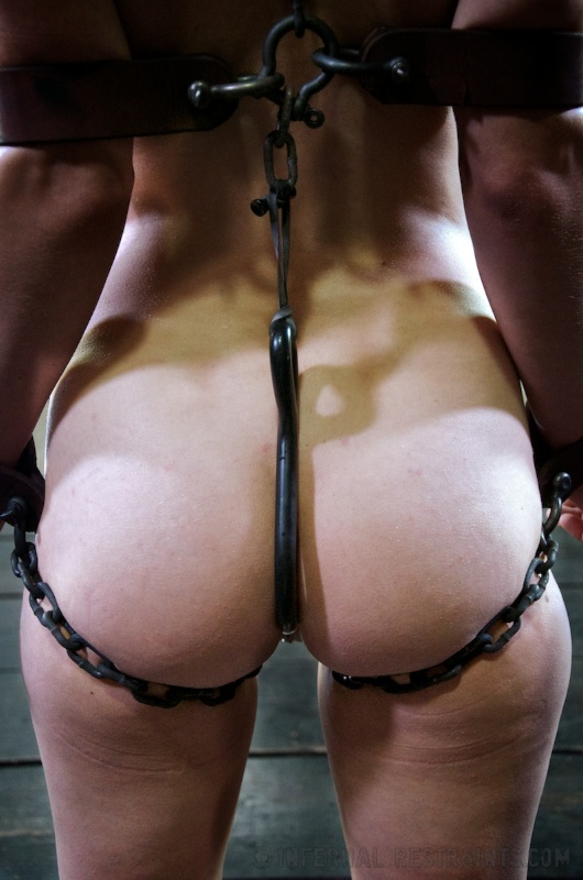 BDSM girl is bound with chains and there is a hook shoved into her ass