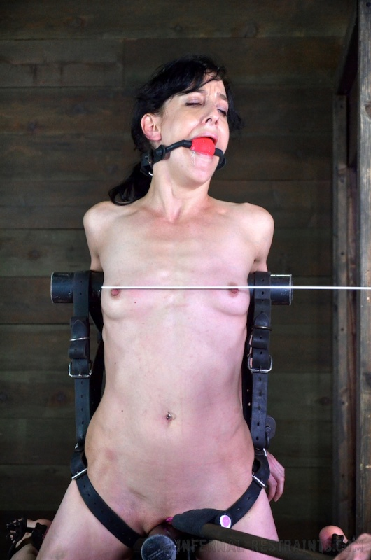 Girl is bound with steel and her tiny tits are getting whipped