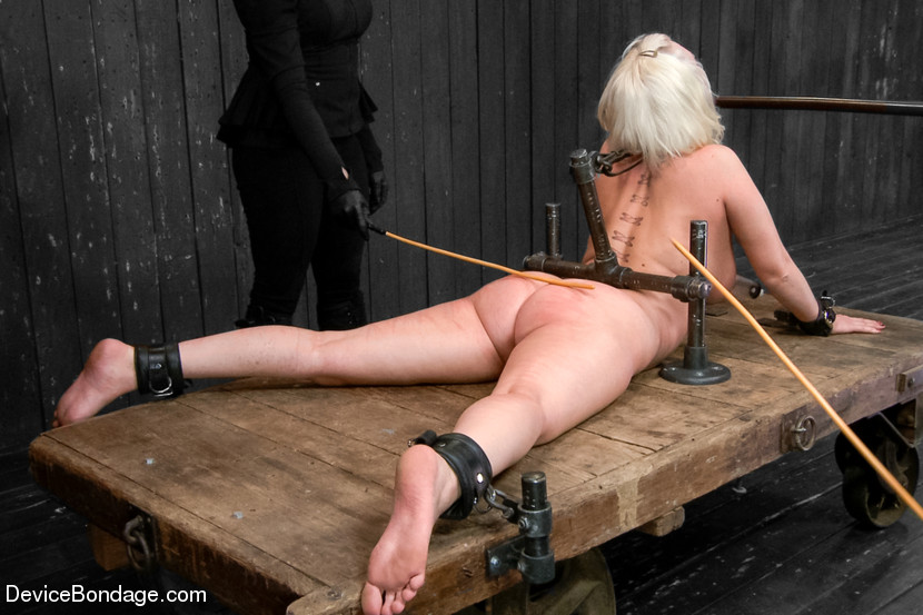 Girl is cuffed to the back-bending BDSM rack and her ass is caned by two men