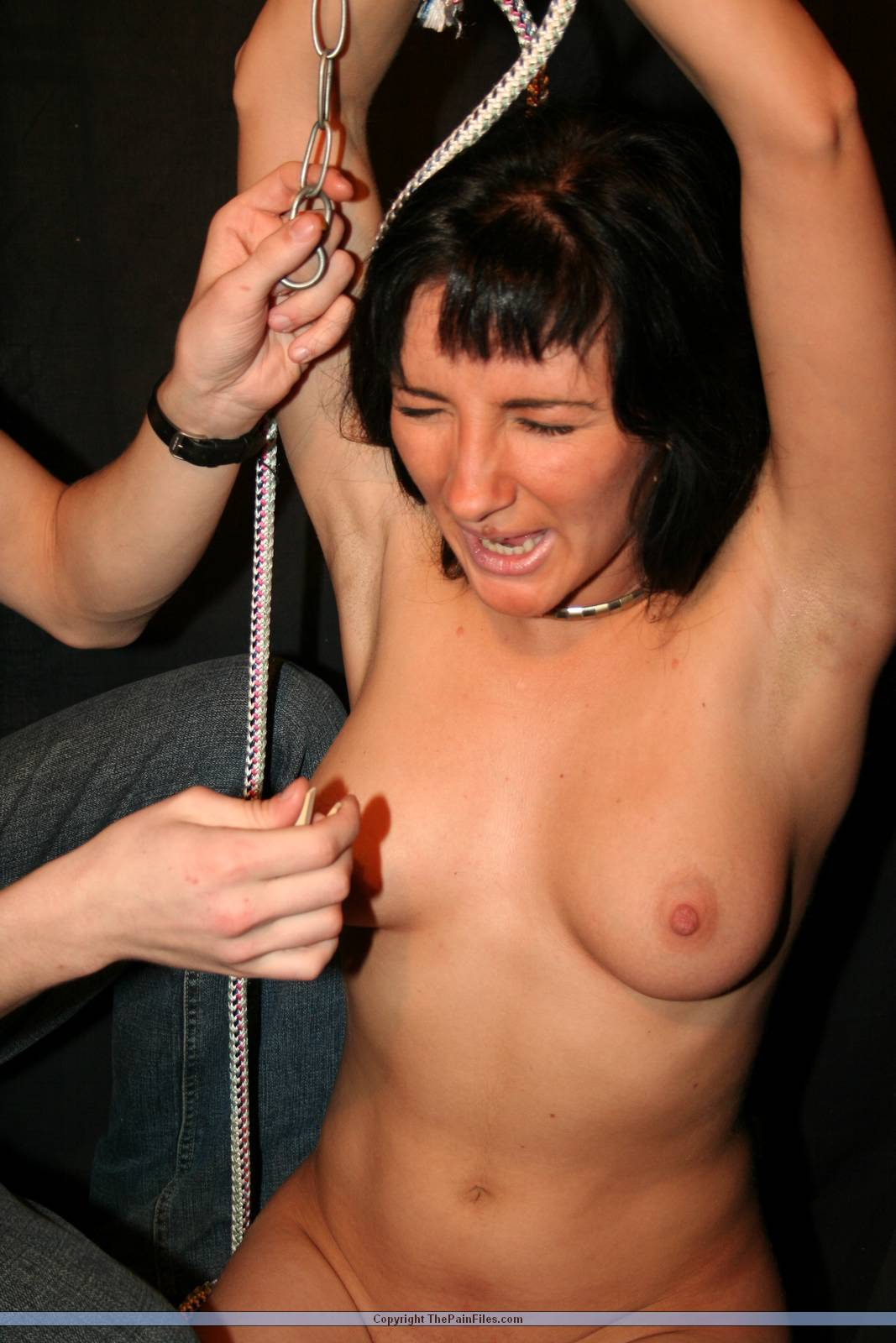 Naked girl is screaming loud in anticipation of a BDSM torture to be performed to her tits