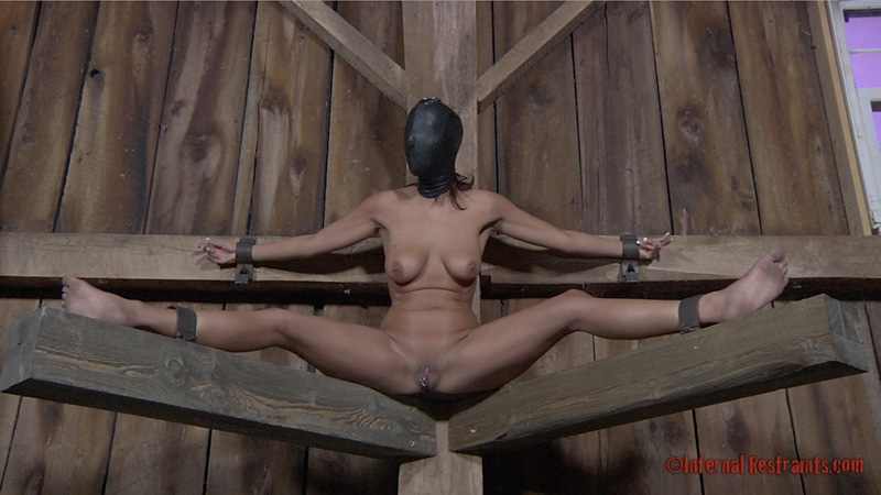 Spread wide and clamped, blindfolded woman is to be tortured on the BDSM rack