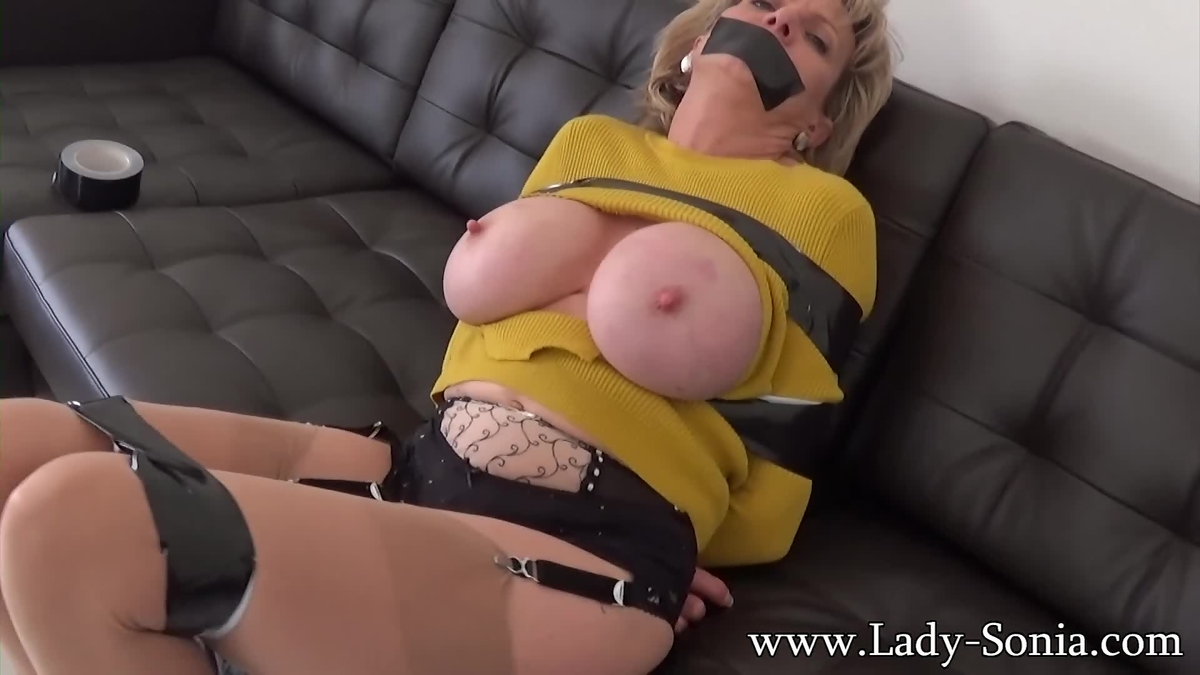 Busty MILF submissive is bound tightly and gagged with duct tape