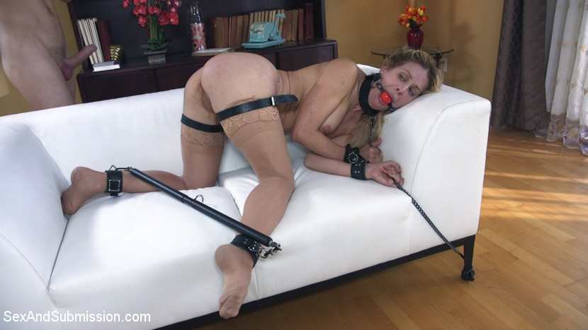Cherie DeVille is put in extreme bondage with leather belts and BDSM spread-bar