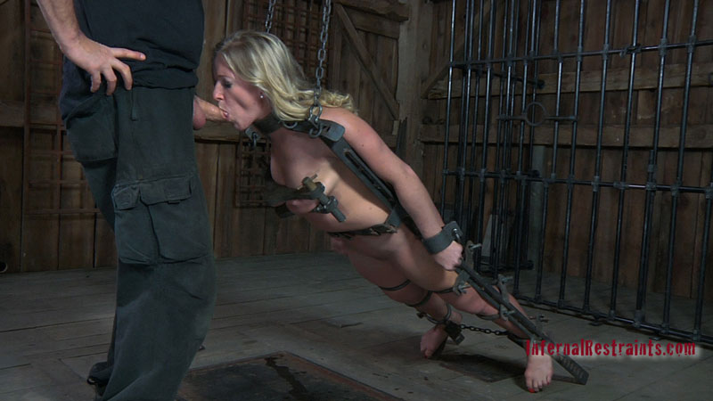 BDSM blowjob training for the nude girl that is placed into bizarre medieval restraining device