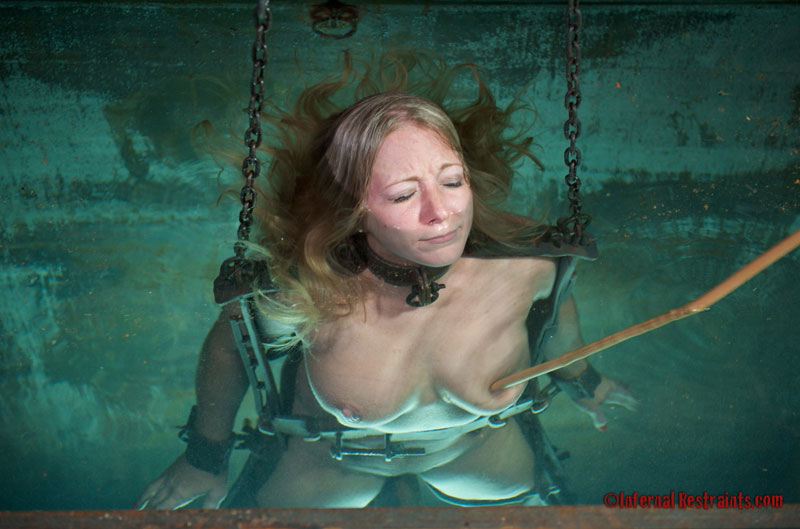 Subjecting BDSM slave to drowning torture by dipping her into deep water while helpless
