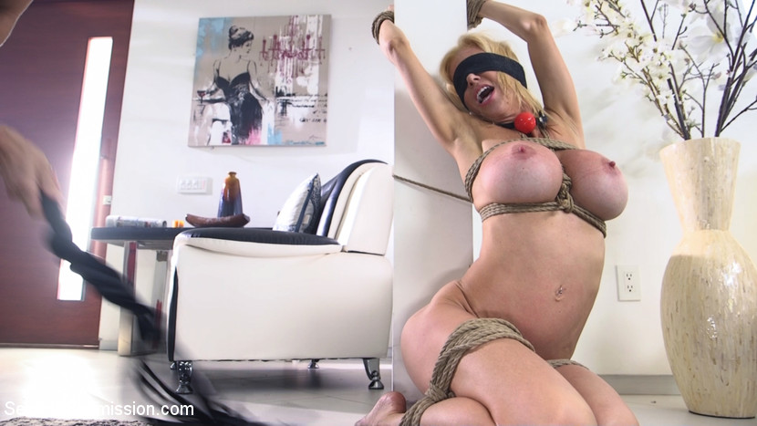 Naked MILF is restrained with rope bondage, put on her knees and blindfolded