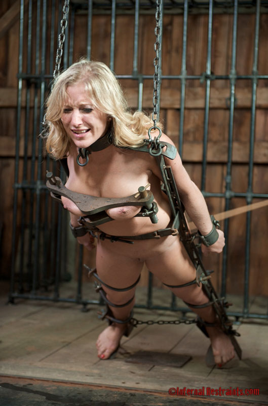 Lovely gal is stripped down and locked into the bizarre medieval torture device made of heavy steel