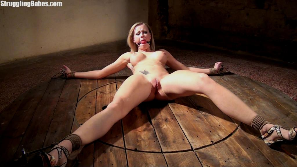 Spread-eagled girl is all naked but wearing a pair of sexy high heel shoes