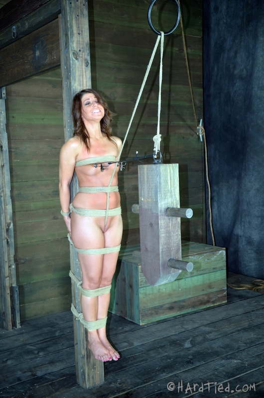 Nude girl is tied to the pole and tight crotch rope is put into her pussy for this torture