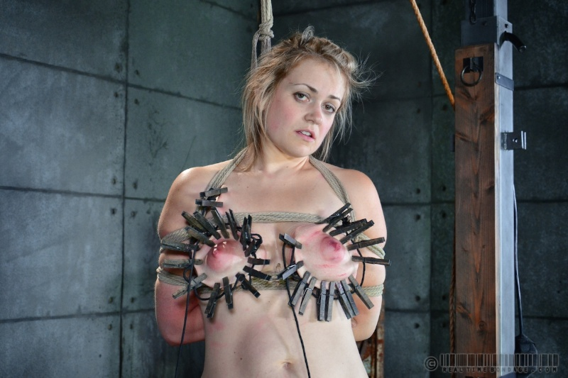 Helpless girl is having dozens of clothespegs placed over her tits and ready for instant ripping