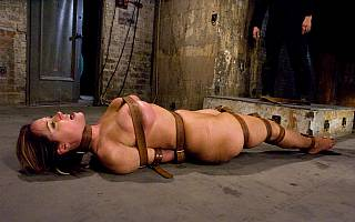 Helpless bondage slave Christina Carter lies on the dirty floor