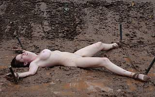 Tied girl lying in the mud
