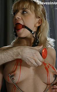 Ball gagged girl enjoys the hot wax on her tits