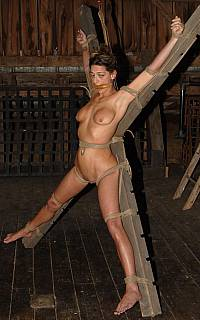 Tied to the cross for BDSM torture