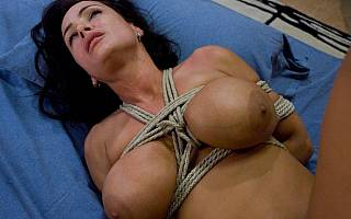 Woman with big tits is tied to bed
