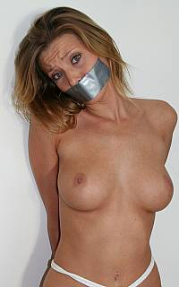 Abductor is having his MILF slave tape gagged