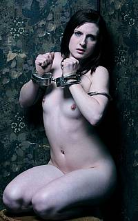 Handcuffed woman kneeling nude