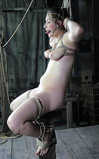 Tied girl sitting on top of wooden pole