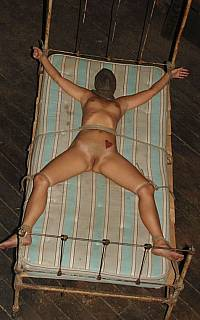 Tied spread eagle to bed