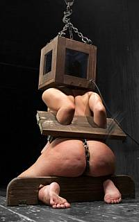 Girl is helplessly bound with wooden stocks