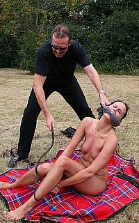 Woman is shackled and whipped outdoors