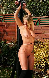Backyard whipping of the nude and bound woman