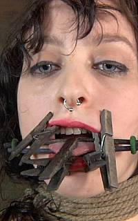Gagging girl with clothes pegs