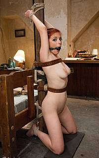 Captive girl is bound to the pole