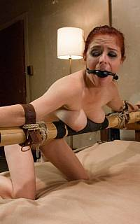 Spread-bound redhead posing gagged in bed