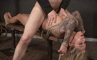 Curvy slut is tied to the bench and fucked in between her tits