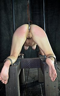 Woman is ass-hooked while clamped to BDSM rack
